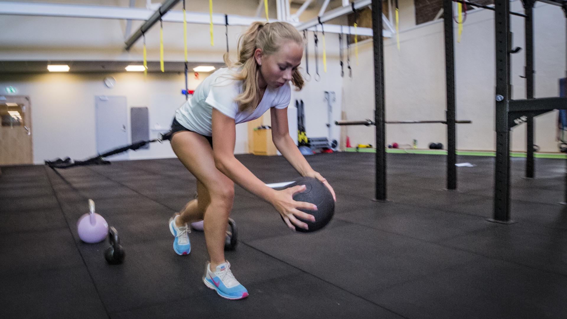 Ung tjej tränar stabilitet och styrka med gummiband och medicinboll
