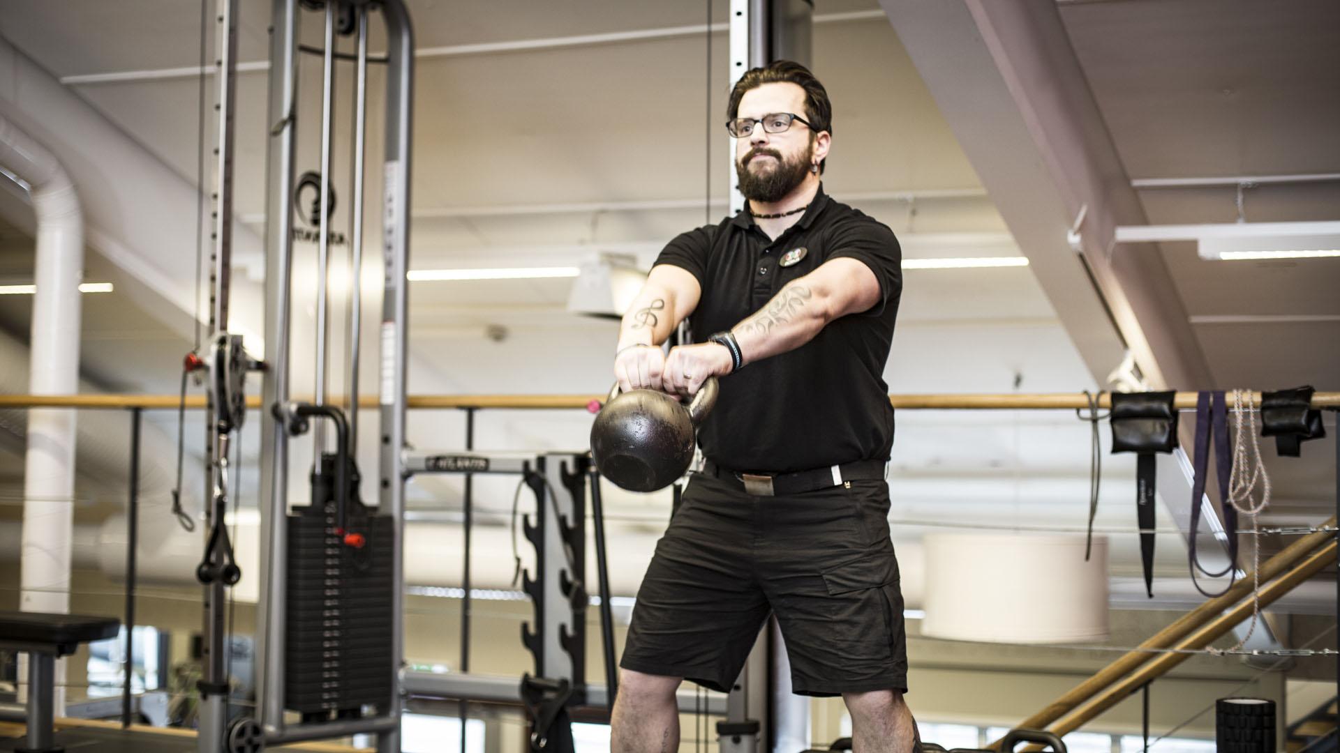 Kraftfull man med glasögon som demonstrerar hur man hanterar kettlebellen