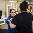 Kvinnlig sjukgymnast hjälper patient med styrketräning i gymmet