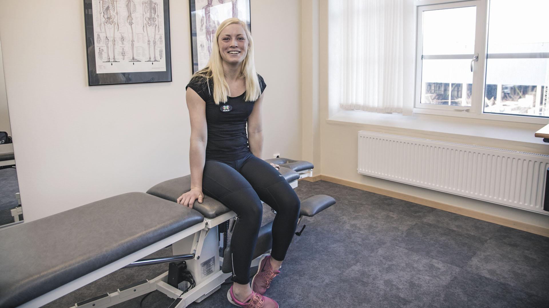 Foto på kvinnlig Personlig Tränare sittandes på behandlingsbänk