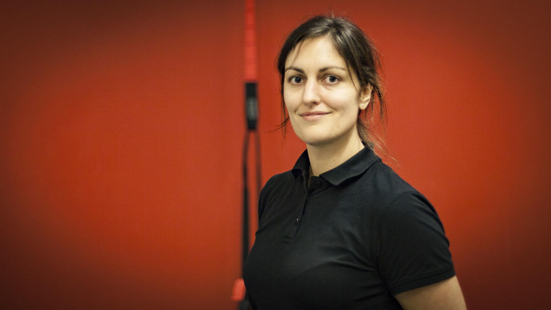 Porträtt av kvinnlig anställd med röd bakgrund