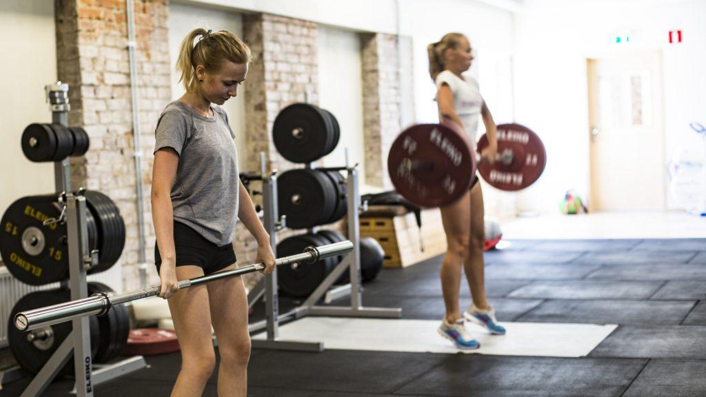 Två tjejer på gymmet som slipar på de olympiska lyften - frivändningar